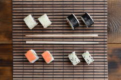 Sushi rolls and wooden chopsticks lie on a bamboo straw serwing mat. Traditional Asian food. Top view.  royalty free stock photography