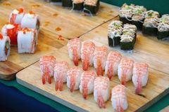 Sushi and Rolls on Wooden Cutting Board. Assorted Sushi and Rolls on Wooden Cutting Board royalty free stock photography
