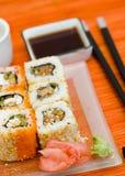 Sushi (rolos) em uma placa Fotos de Stock Royalty Free