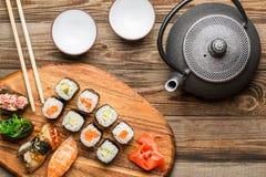 Sushi, rotoli, teiera e tazze sulla tavola fotografie stock