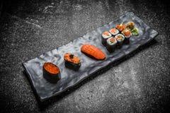 Sushi, rotolo e bastoncino giapponesi dei frutti di mare su una banda nera Immagini Stock