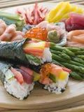 Sushi roulés par main de fruits de mer et de légume photographie stock