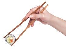 Sushi - roulis avec des baguettes d'isolement Photographie stock