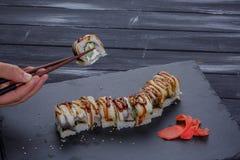 Sushi - rulle på en svart platta med hållande pinnar för manhand över svart bakgrund Royaltyfri Fotografi