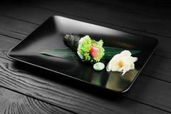 Sushi sabroso japonés del temaki en fondo negro Imagen de archivo