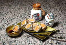 Sushi,sake on a grnite counter. Sushi plate, chop sticks and saki cups on a granite background Royalty Free Stock Photos