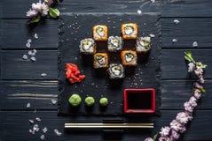 Sushi, sakuratak, sojasaus op een zwarte lijst royalty-vrije stock afbeeldingen
