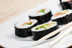 Sushi with salmon, avocado, rice in seaweed and chopsticks on a plate. Royalty Free Stock Photos