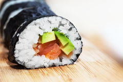 Sushi with salmon, avocado, rice in seaweed and chopsticks on wooden table Stock Photos