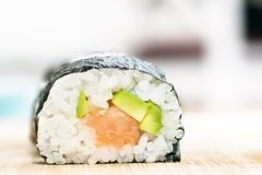 Sushi with salmon, avocado, rice in seaweed and chopsticks on wooden table Royalty Free Stock Photo