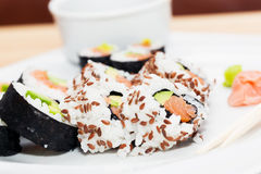Sushi with salmon, avocado, rice in seaweed served with wasabi and ginger. Stock Image