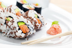 Sushi with salmon, avocado, rice in seaweed served with wasabi and ginger. Stock Photos