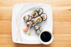 Sushi with salmon, avocado, rice in seaweed served with wasabi and ginger. Royalty Free Stock Photos