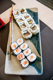 Sushi with salmon, avocado and tuna fish on a plate with chopsticks Royalty Free Stock Photography
