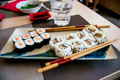 Sushi with salmon, avocado and tuna fish on a plate with chopsticks Royalty Free Stock Photos