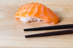 Sushi salmon and black chopsticks on wood background, Japanese f Royalty Free Stock Photos