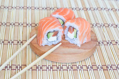 Sushi with salmon, caviar(mayonnaise) and a cucumber. Sushi with salmon, caviar and a cucumber on a round, wooden stand Stock Images