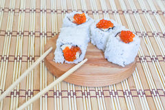 Sushi with salmon, caviar(mayonnaise) and a cucumber. Sushi with salmon, caviar and a cucumber on a round, wooden stand Royalty Free Stock Images