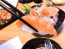 Sushi. Salmon fish dish japan rice food wood chopsticks background Royalty Free Stock Images