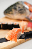 Sushi and salmon head. Sushi on a cutting boars, with a salmon head on background and some salmon sashimi served on the knife blade on foreground Royalty Free Stock Photo