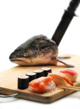 Sushi and salmon head. Sushi on a cutting boars, with a salmon head and a knife on the background and chopstick Royalty Free Stock Photos