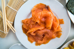 Sushi - Salmon prepared on a dish. Fine salmon fillet prepared for sushi on a white plate Royalty Free Stock Image