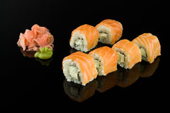 Sushi with salmon. Sushi roll with salmon and Philadelphia cheese wasabi ginger on a black background with reflection Royalty Free Stock Photography