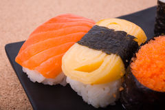 Sushi, salmon, shrimp eggs, Tamagoyaki, Ebiko, Ebi Nigiri. This is surrounded by Maki Sushi and pages. Focus salmon. Blurred background, there are some points Stock Image