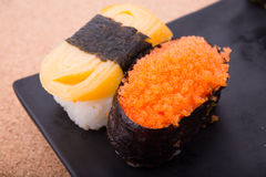 Sushi, salmon, shrimp eggs, Tamagoyaki, Ebiko, Ebi Nigiri. This is surrounded by Maki Sushi and pages. Focus salmon. Blurred background, there are some points Stock Photography