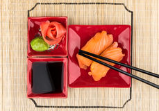 Sushi with salmon, soy sauce, ginger, wasabi on bamboo mat Stock Image