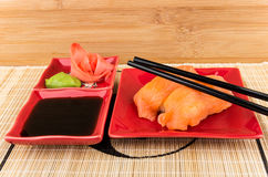 Sushi with salmon, soy sauce, ginger, wasabi on mat Stock Photography