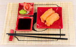 Sushi with salmon, soy sauce, ginger, wasabi on mat Royalty Free Stock Images