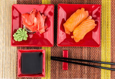 Sushi with salmon, soy sauce, ginger, wasabi on mat Royalty Free Stock Photography
