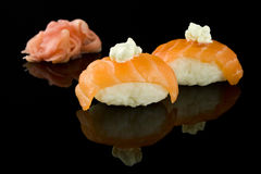 Sushi with salmon. Sushi two pieces with salmon on a background of ginger and wasabi on black with reflection Royalty Free Stock Photography