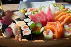 Sushi and Sashimi. Japanese cuisine: prepared and delicious sushi and sashimi closeup on wooden tray royalty free stock photography