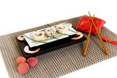 Sushi, sashimi. Plate with traditional Japanese sushi, sashimi rolls, shrimps, shop sticks on the side of the plate.  Studio shot Royalty Free Stock Photography
