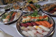 Sushi, sashimi, rollos en las bandejas y bocados fríos Fotos de archivo
