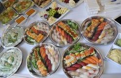 Sushi, sashimi, rollos en las bandejas y bocados fríos Imagenes de archivo