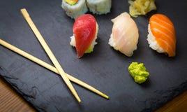 Sushi and Sashimi rolls on a black stone slatter. Fresh made Sushi set with salmon, prawns, wasabi and ginger. Traditional Japanes Stock Photography