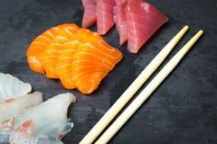 Sushi and Sashimi rolls on a black stone slatter. Fresh made Sushi set with salmon, prawns, wasabi and ginger. Traditional Japanes Stock Photo