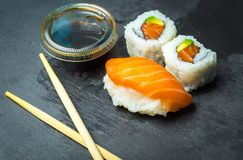 Sushi and Sashimi rolls on a black stone slatter. Fresh made Sushi set with salmon, prawns, wasabi and ginger. Traditional Japanes Royalty Free Stock Images