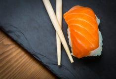 Sushi and Sashimi rolls on a black stone slatter. Fresh made Sushi set with salmon, prawns, wasabi and ginger. Traditional Japanes Royalty Free Stock Photo