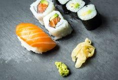 Sushi and Sashimi rolls on a black stone slatter. Fresh made Sushi set with salmon, prawns, wasabi and ginger. Traditional Japanes Royalty Free Stock Photography