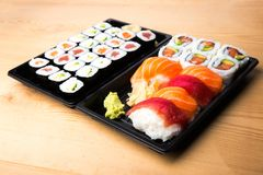 Sushi and Sashimi rolls on a wooden table. Fresh made Sushi set with salmon, prawns, wasabi and ginger. Traditional Japanese cuisi Royalty Free Stock Images