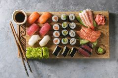 Sushi sashimi set. Sushi Set nigiri sashimi and sushi rolls on wooden serving board with soy sauce and chopsticks over grey concrete background. Flat lay, space stock images