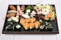 Sushi sashimiuppsättning på den svarta plattan Arkivfoton