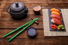 Sushi-Satz diente auf grauer Steinkandidatenliste mit Sojasoße, grauer Teekanne und Tasse Tee Stockfoto