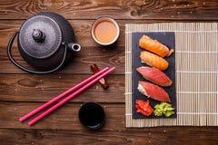 Sushi-Satz diente auf grauer Steinkandidatenliste mit Sojasoße, grauer Teekanne und Tasse Tee Stockfotos