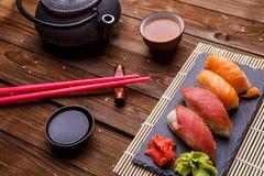 Sushi-Satz diente auf grauer Steinkandidatenliste mit Sojasoße, grauer Teekanne und Tasse Tee Lizenzfreie Stockbilder
