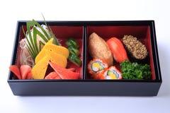 Sushi-Satz in hölzernem Bento (japanischer Lunchbox) lokalisiert auf Weiß Stockfotos